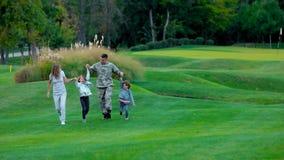 Padre militar de la vista delantera con su caminar y salto familiy felices almacen de video