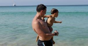 Padre mojado con el hijo en fondo del mar con la nave metrajes
