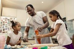 Padre moro e figlie sveglie che cucinano pizza per la cena fotografia stock
