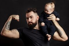 Padre muscular que detiene a su pequeño bebé Fotografía de archivo