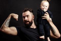 Padre muscular que detiene a su pequeño bebé Fotos de archivo libres de regalías