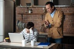 Padre muy atento observando proceso que tachona de su hijo Foto de archivo