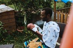 Padre negro que detiene a su bebé de la raza mixta fotos de archivo libres de regalías