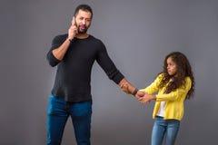 Padre nero che parla sul suo telefono mentre sua figlia che tira il suo Immagine Stock Libera da Diritti