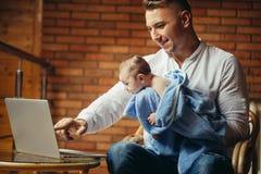 Padre With Newborn Baby que trabaja de hogar usando el ordenador portátil Imágenes de archivo libres de regalías