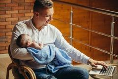 Padre With Newborn Baby que trabaja de hogar usando el ordenador portátil Imagenes de archivo