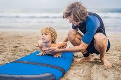 Padre o istruttore che insegna a suo figlio di 4 anni a come praticare il surfing dentro fotografia stock libera da diritti