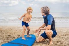 Padre o istruttore che insegna a suo figlio di 4 anni a come praticare il surfing dentro fotografie stock libere da diritti