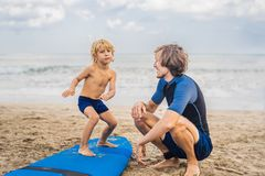 Padre o istruttore che insegna a suo figlio di 4 anni a come praticare il surfing dentro immagine stock