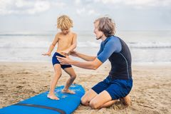 Padre o istruttore che insegna a suo figlio di 4 anni a come praticare il surfing dentro immagine stock libera da diritti