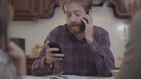 Padre ocupado barbudo que habla por el teléfono celular, él no tiene ninguna hora y no presta la atención a su hija y esposa E almacen de metraje de vídeo