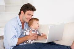 Padre ocupado que trabaja en la computadora portátil Foto de archivo libre de regalías