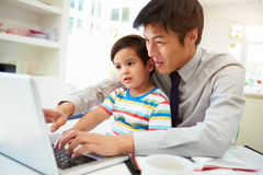Padre ocupado Working From Home con el hijo fotos de archivo
