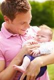 Padre orgulloso Holding Baby Daughter en jardín Fotografía de archivo
