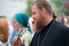 Padre ortodoxo que dá a cruz para beijar ao paroquiano Imagem de Stock