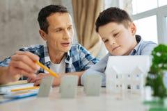 Padre piacevole che spiega i principi di lavoro dei pannelli solari Immagine Stock