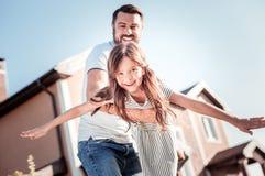 Padre piacevole preoccupantesi che sorride e che sostiene sua figlia fotografie stock
