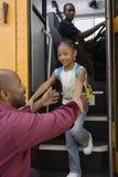 Padre Picking Up Daughter en la parada de autobús Imágenes de archivo libres de regalías