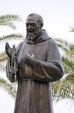 Padre Pio. Letojanni, Sicily, Italy - September 26, 2012: Bronze Statue of the catholic saint Padre Pio, with rosaries Royalty Free Stock Image