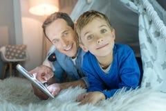 Padre positivo e hijo encantados que juegan junto Imagen de archivo