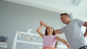 Padre positivo y pequeña hija que bailan en casa metrajes