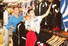 Padre positivo y su hijo que eligen la ropa del deporte Fotografía de archivo libre de regalías