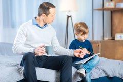 Padre preoccupantesi che dà a suo figlio le punte del disegno immagini stock