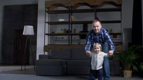 Padre preoccupantesi che insegna a poca figlia a camminare stock footage