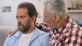 Padre preoccupantesi che sostiene suo figlio che avverte divorzio, problemi sanitari degli uomini video d archivio