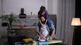 Padre preoccupantesi con il figlio sui vestiti rivestenti di ferro della spalla archivi video