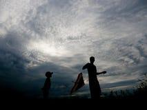 Padre preoccupantesi e piccolo figlio che lanciano un aquilone al tramonto Immagini Stock Libere da Diritti