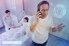 Padre preoccupato che ha una conversazione del telefono mentre visitando sua figlia malata in un ospedale fotografia stock