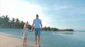 Padre profilato e figlia felici che giocano e che si divertono sulla spiaggia al tramonto Movimento lento Infanzia felice della f stock footage