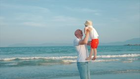 Padre profilato e figlio felici che giocano e che si divertono sulla spiaggia al tramonto Movimento lento Infanzia felice della f stock footage