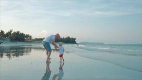 Padre profilato e figlio felici che giocano e che si divertono sulla spiaggia al tramonto Movimento lento Infanzia felice della f archivi video