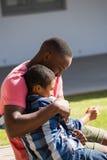 Padre que abraza a su hijo en el patio trasero Foto de archivo libre de regalías