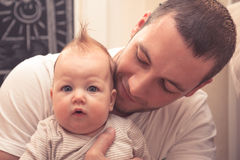 Padre que abraza a su pequeño bebé El padre está mirando en el bebé, bebé está mirando en cámara Bebé con corte de pelo divertido Fotografía de archivo libre de regalías