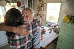 Padre que acoge con satisfacción a la hija en la cocina fotografía de archivo libre de regalías