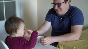 Padre que alimenta a la hija linda del bebé en casa con una cuchara 4k almacen de video