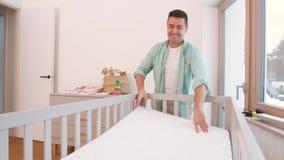 Padre que arregla la cama de bebé con el colchón en casa metrajes