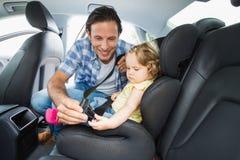 Padre que asegura al bebé en el asiento de carro foto de archivo libre de regalías