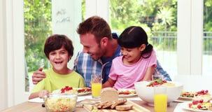 Padre que ayuda a niños mientras que come el almuerzo metrajes
