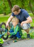 Padre que ayuda a su bicicleta del arreglo del hijo foto de archivo