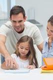 Padre que ayuda a su hija a dibujar Imagenes de archivo