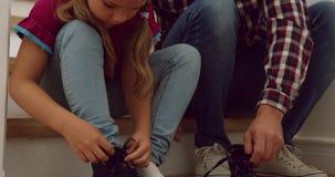Padre que ayuda a su hija a llevar los zapatos en las escaleras en un hogar cómodo 4k almacen de metraje de vídeo