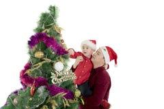 Padre que ayuda a su hijo a adornar el árbol de navidad Imagenes de archivo