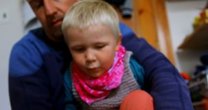 Padre que ayuda a su hijo a llevar calcetines en el dormitorio en casa 4k almacen de video