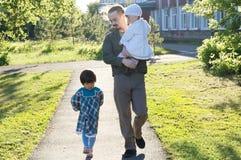 Padre que camina con las hijas en el día soleado papá y muchachas que enlazan la relación papá feliz con dos niños en el parque a fotografía de archivo libre de regalías