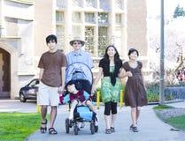 Padre que camina con sus niños al aire libre. Hijo discapacitado en rueda Imagen de archivo libre de regalías