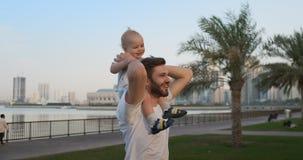 Padre que camina con un niño que se sienta en el cuello metrajes